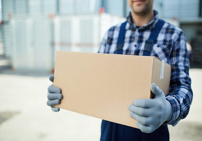 worker holding a cardboard box with gloves on